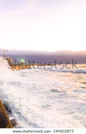 The sea on the sheashore in a city of South Africa, with waves during sunset. - stock photo