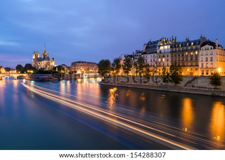 The Seine in Paris, France at Night with the Notre Dame Cathedral in the Distance - stock photo