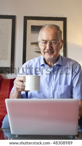 The senior man uses his laptop with a cup of coffee in the living room - stock photo