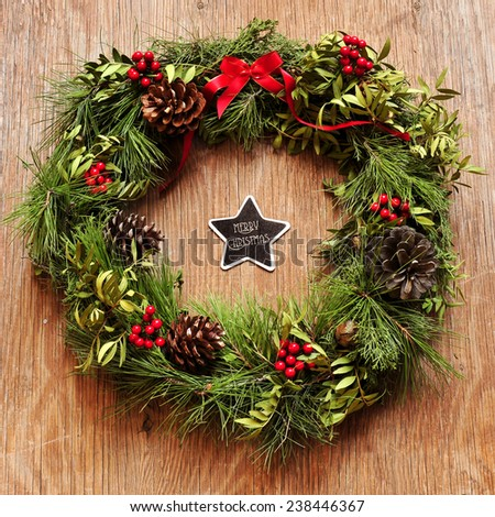 the sentence merry christmas written in a star-shaped chalkboard and a natural christmas wreath hanging on a rustic wooden door - stock photo