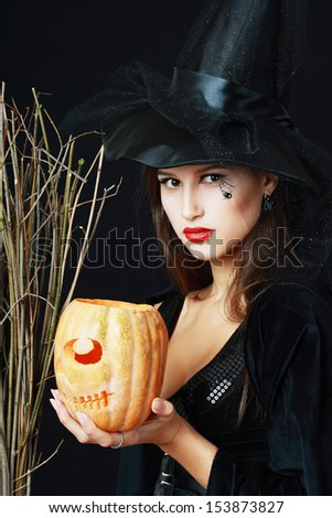 The serious brunette witch with a broom and pumpkin over black background in studio - stock photo