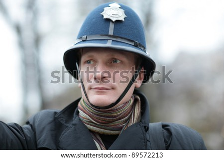The serious man posing in british police hat - stock photo
