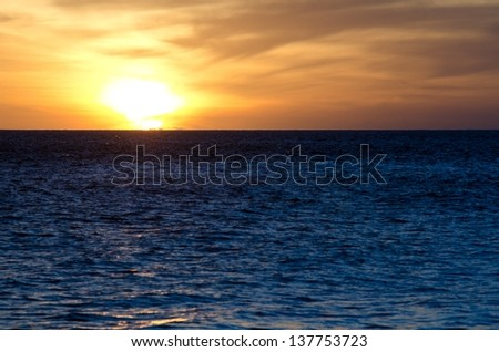 the setting sun behind clouds and a blue ocean at Big Beach on the Island of Maui.  *this was shot as is*  No post - stock photo