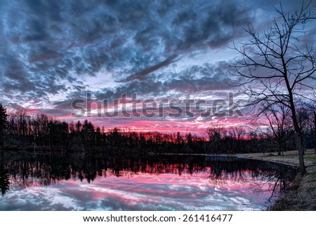 The setting sun paints the sky with vivid and dramatic colors that is reflected on a small Indiana pond in Sodalis Nature Park. - stock photo