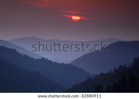 The setting sun slipping behind some clouds looks over the receding ridges of the Great Smoky Mountain National Park as seen from the Morton Overlook. This view is the classic Smoky Mountain scene. - stock photo