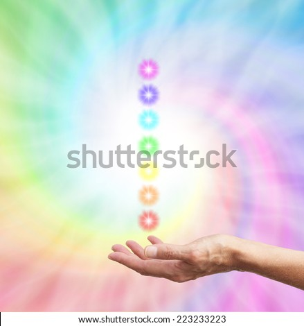 The Seven Chakras  -  healer's hand  palm up with a stack of chakra star bursts on a rainbow spiral background - stock photo