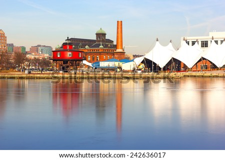 The Seven Foot Knoll Lighthouse at sunset in Baltimore Inner Harbor. Colorful reflections of waterfront buildings at Inner Harbor in Baltimore, Maryland. - stock photo
