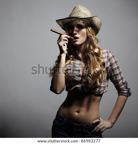 The sexy blonde woman with amazing hair in a hat and with a cigar in an image of the American cowboy. Fashion portrait. - stock photo
