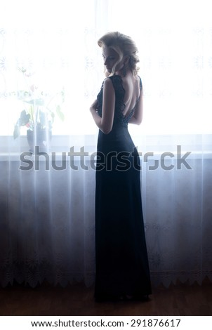 the sexy elegant women with a fashionable hairstyle poses near the window in black dress - stock photo