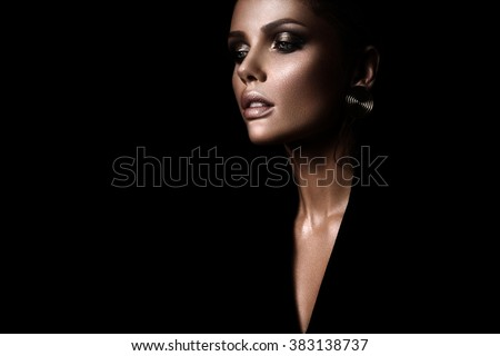 the sexy strict woman with makeup and a fashionable  hairstyle poses in studio on black background - stock photo