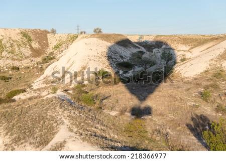 The shadow of a hot air balloon over rock landscape in Cappadocia - stock photo