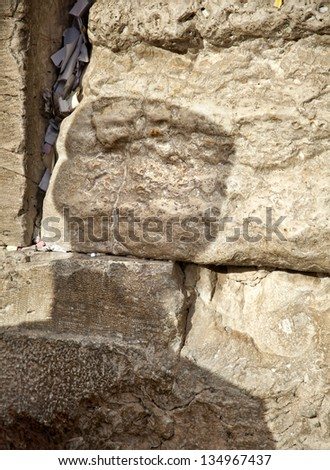 The shadow of an orthodox Jewish man on the sacred Wailing Wall in the old city of Jerusalem, Israel. Letters with wishes and pleading to god can be seen in the large crack between the ancient stones. - stock photo
