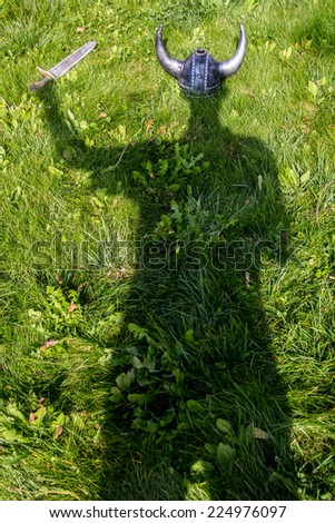 The shadow of the viking on the grass - stock photo