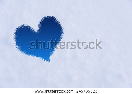 The shape of heart on the snow. Closeup shot. - stock photo