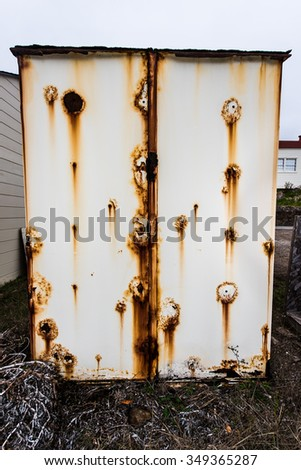 The side of an old metal storage box is rusted in many patterns - stock photo