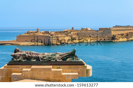 The Siege Bell monument with Fort Ricasoli in the background. - stock photo