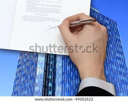 The Signature of Business Contract in front the Skyscraper on the blue Sky - stock photo