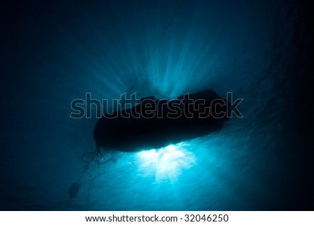 The Silhouete of a dive boat on a mooring line. Red Sea, Egypt. - stock photo