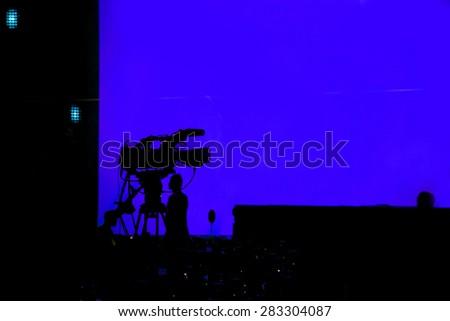 The silhouette camcorder (vdo camera) over blue screen - stock photo