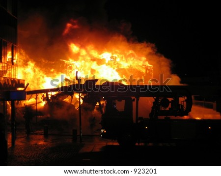 The silhouette of a firetruck with a burning house in the background - stock photo