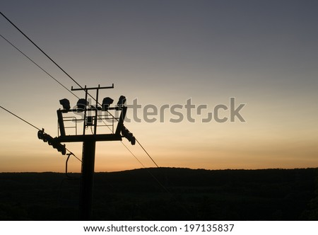 The silhouette of a hydro pole at sunset. - stock photo