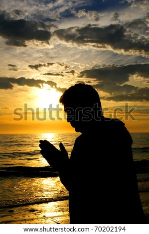 The silhouette of a man with his hands folded in prayer at the ocean at sunset. - stock photo