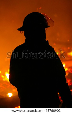 The silhouette of Fire Fighter watching a fire - stock photo
