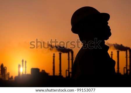 The silhouette of oil refinery worker at sunset - stock photo
