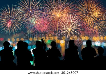 The silhouette of reporter photograph the Fantastic festive new years colorful fireworks on cityscape blurred photo bokeh,project success, holiday concept - stock photo