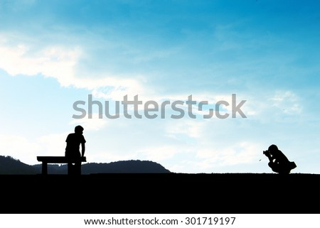The silhouette of siting photographer take a picture of siting man with blue cloudy sky background - stock photo