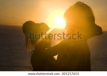 The silhouette of the couple embracing each other at dusk - stock photo