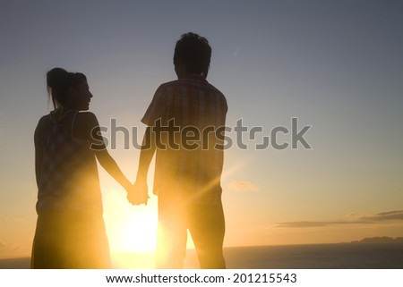 The silhouette of the couple holding hands in the evening - stock photo
