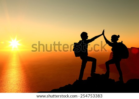 The Silhouette of two man with success gesture standing on the top of mountain - stock photo