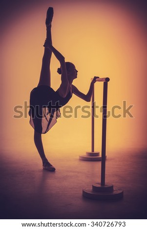 The silhouette of young ballerina stretching on the bar on orange background - stock photo