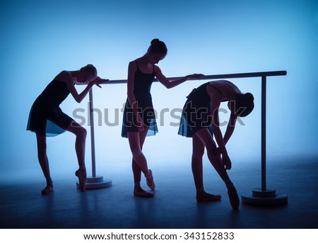 The silhouettes of young ballerinas stretching on the bar on blue background - stock photo