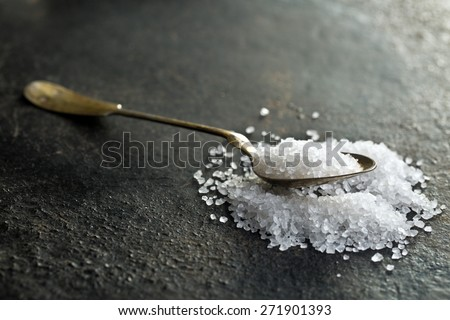 the silver spoon with white salt  - stock photo