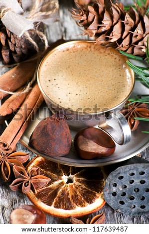 The silvers cup of coffe with cinnamon, anise, cone and chestnuts on the woody background - stock photo
