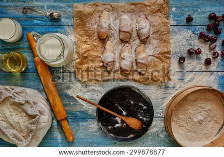The situation in confectionery, will cook bagels stuffed with cherries, put them on paper for baking, lies next to the flour, milk is in the decanter - stock photo