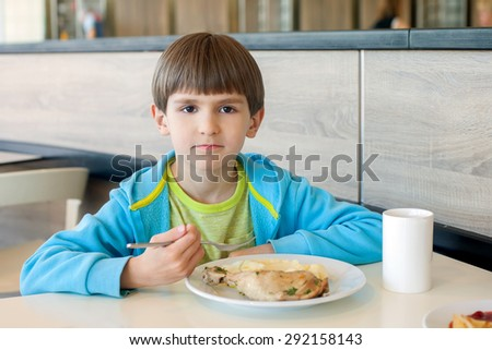 The six years boy eats chicken with mashed potatoes - stock photo