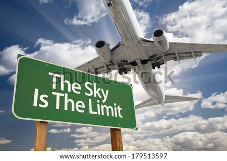 The Sky Is The Limit Green Road Sign and Airplane Above with Dramatic Blue Sky and Clouds. - stock photo
