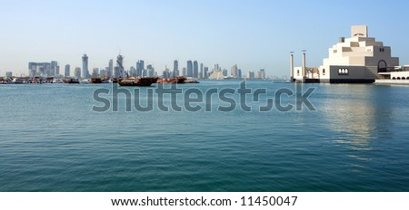 The skyline across Doha Bay in Qatar, with the Islamic museum and dhow harbour in the foreground and the new high-rise district behind. - stock photo