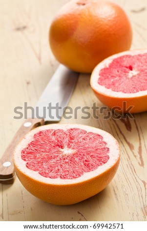 the sliced red grapefruit on kitchen table - stock photo