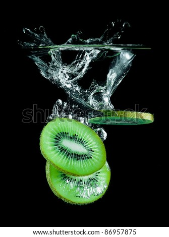 The slices of kiwi falling into water . - stock photo