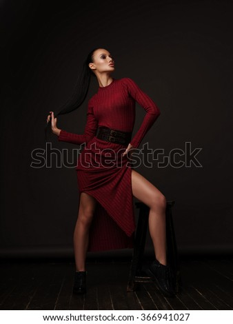 The slim elegant model in the vinous dress and black patent leather boots with slicked straight ponytail and long beautiful legs is posing in the fashion studio - stock photo
