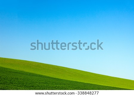 The sloping layered farm fields of a rural landscape on the side of a hill meet a clear blue sky. - stock photo
