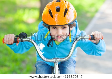 The small boy in blue fleece jacket ride a cycle  - stock photo