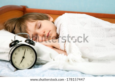The small boy sleep in bed with wake-up clock - stock photo