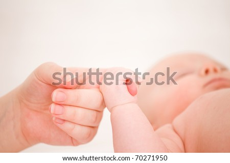 The small child is held by the hand the parent. Care and support. - stock photo