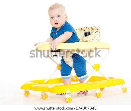 The small child learns to walk by means of Baby walker on a white background. - stock photo