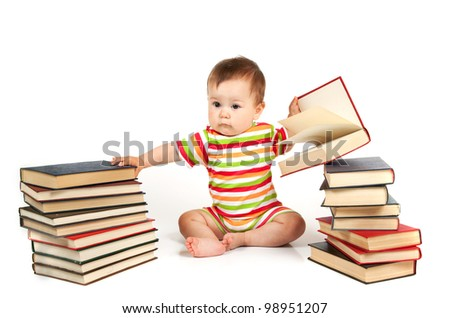 The small child sits near a pile of books - stock photo